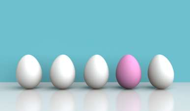 4 white eggs lines up with 1 stand out pink egg on blue background